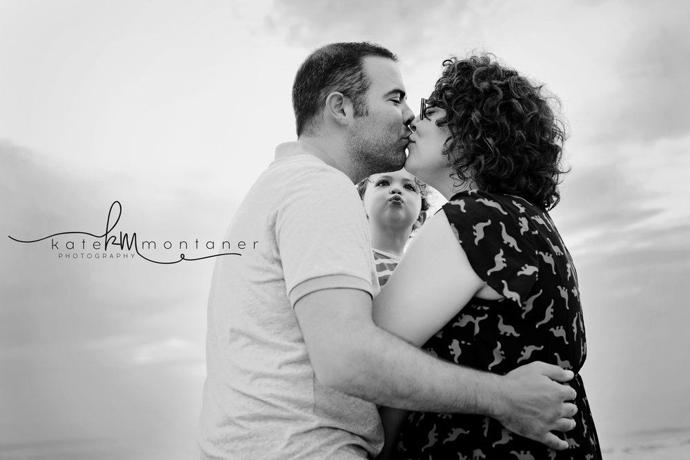 mom-and-dad-kiss-on-beach-little-girl-makes-kissy-face-Kate-Montaner-Photography-black-and-white