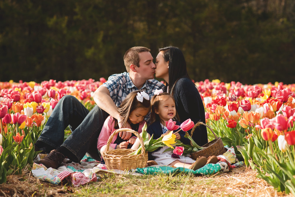 couple-in-love-kiss-with-two-daughters-tulip-session-kate-montaner-photography-family-portraits-northern-virginia