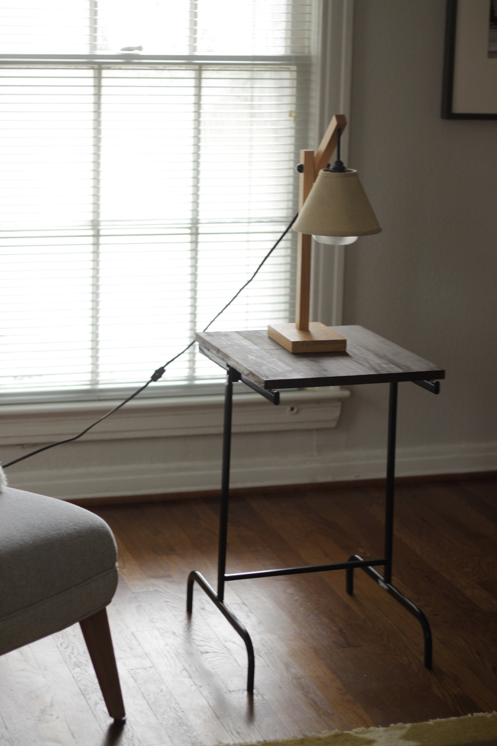 """The table is a slab of pine wood stained and an ikea hamper frame. I'm not clever enough to come up with this on my own, but if you search """"IKEA hamper side table"""" on Pinterest you'll find a million tutorials. The lamp is 5 years old, from World Market."""