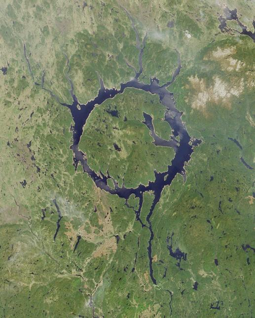 Manicouagan crater, the 'Eye of Quebec' - a view from orbit.  Manic 5 is located along the bottom right of the image, approximately where the longest water tail peters out Public Domain, https://commons.wikimedia.org/w/index.php?curid=372811