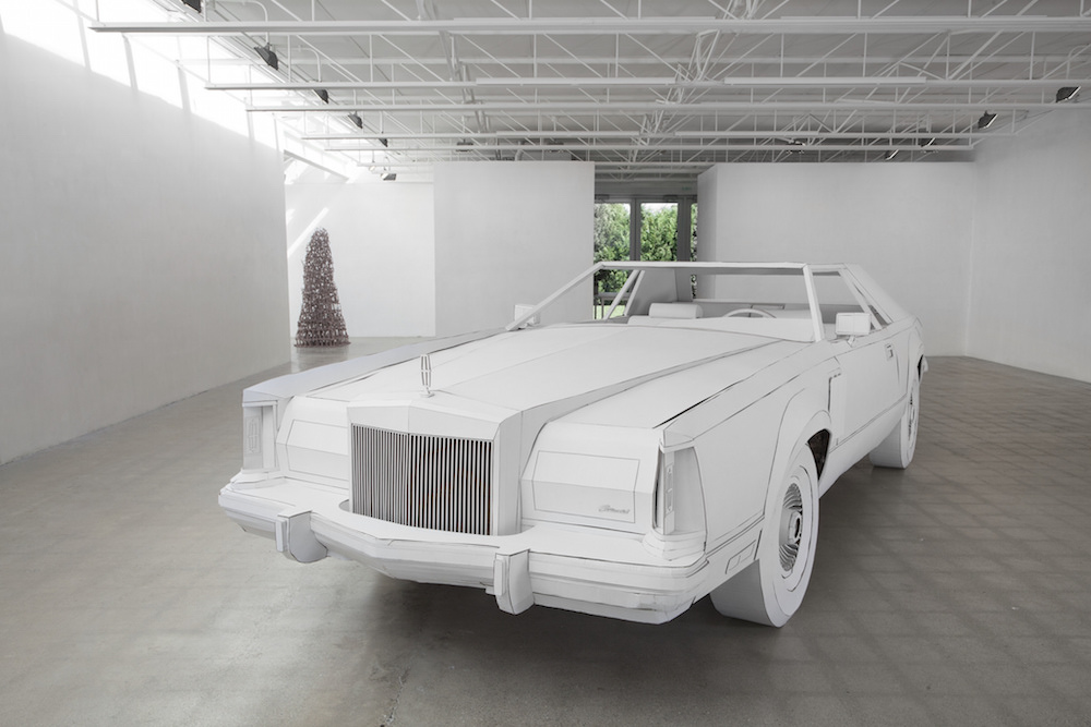 "Shannon Goff,  Miles to Empty  exhibit at Susanne Hilberry Gallery, Ferndale MI, 2015. Foreground:  Miles to Empt y (Lincoln Continental Mark V built full-scale in cardboard), 19 ft x 6 ft 5"" x 4 ft 9"". Background:   Madre,  ceramic. Photo: P.D. Rearick."