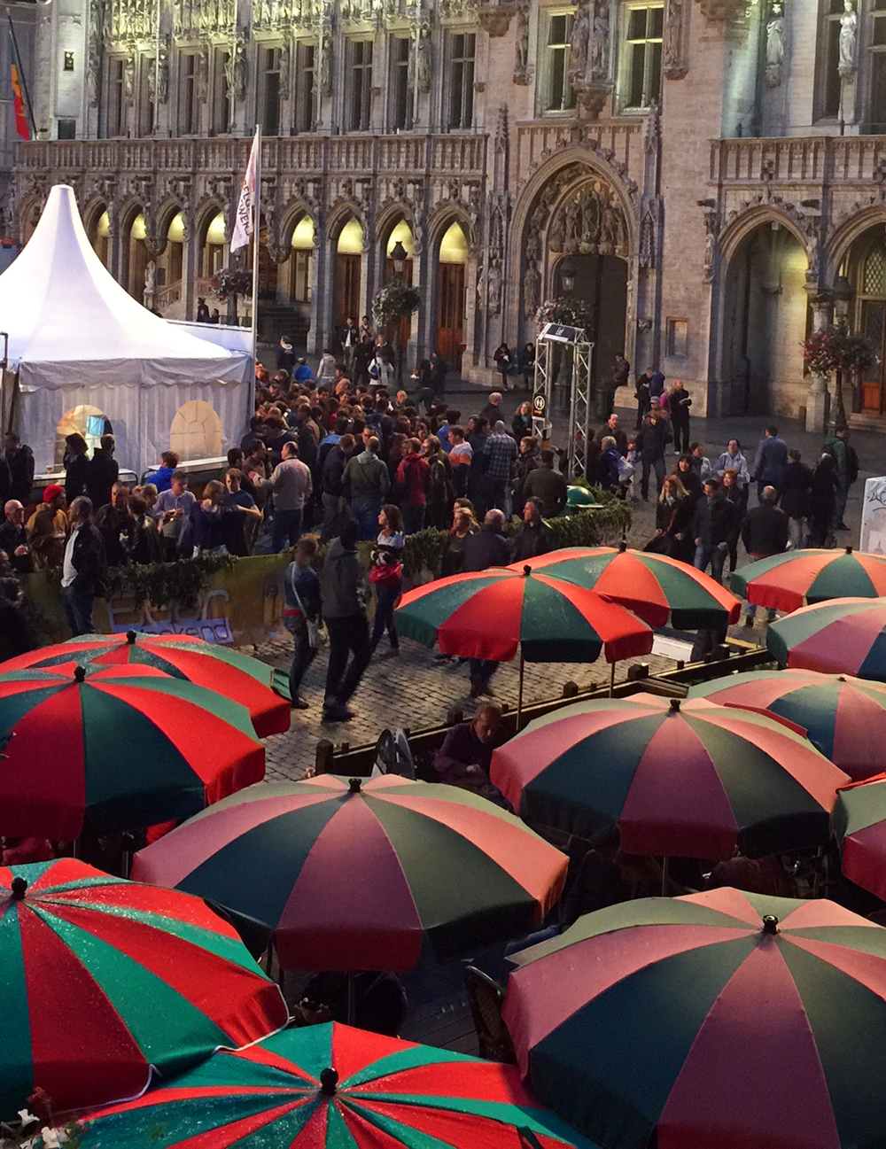 Restaurant umbrellas, beer booth tents, and boulevardiers in front of the Brussels city hall