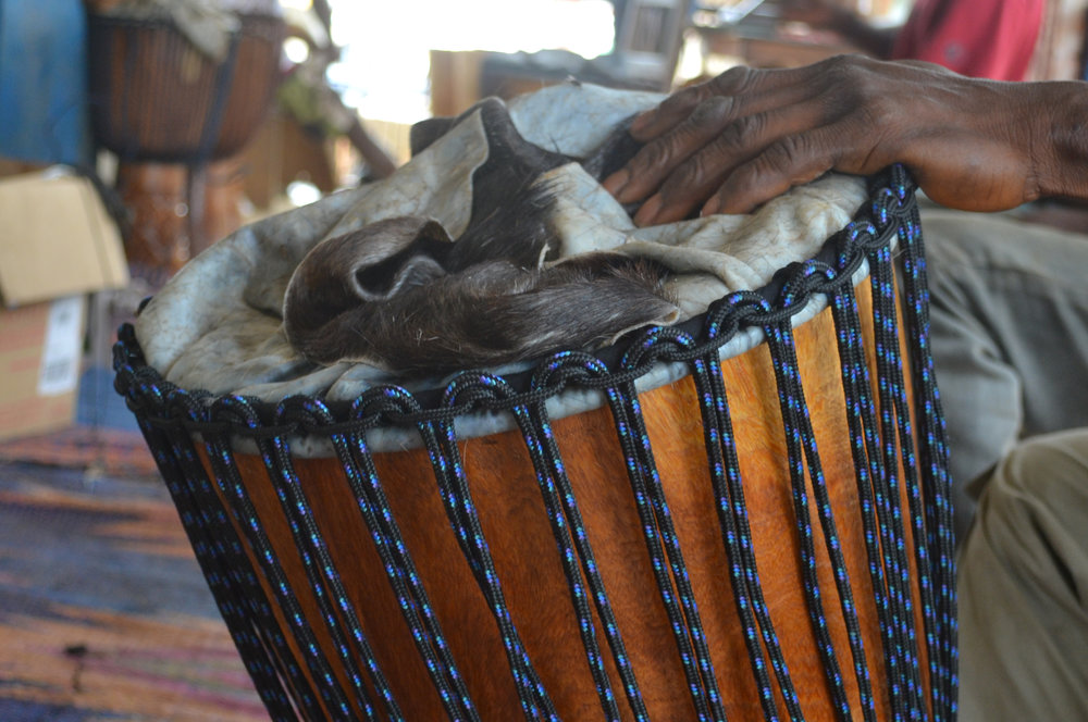 Putting a head on a wula djembe in guinea - make your own at the retreat!