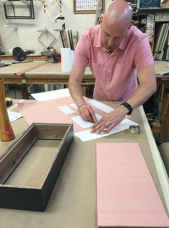 Our framer/owner Eric, mapped out the lining of the shadow box walls. Each side ishand-wrapped with a pink, silk fabric. Eric also, and unintentionally, matched the light pink silk fabric.