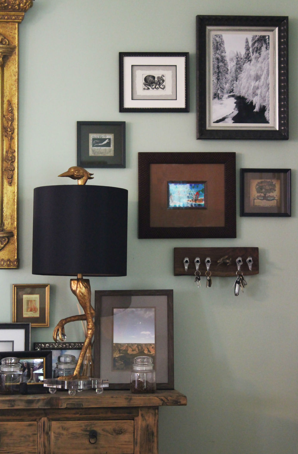 This entryway grouping incorporates an ibis bird lamp and maple spout key rack. Working around three-dimensional pieces can add visual interest to an otherwise flat viewing space.