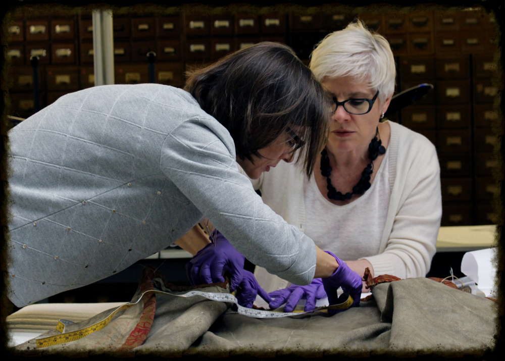 Anne Whitelaw (right) and Cynthia Cooper (left) examining the Metis coat