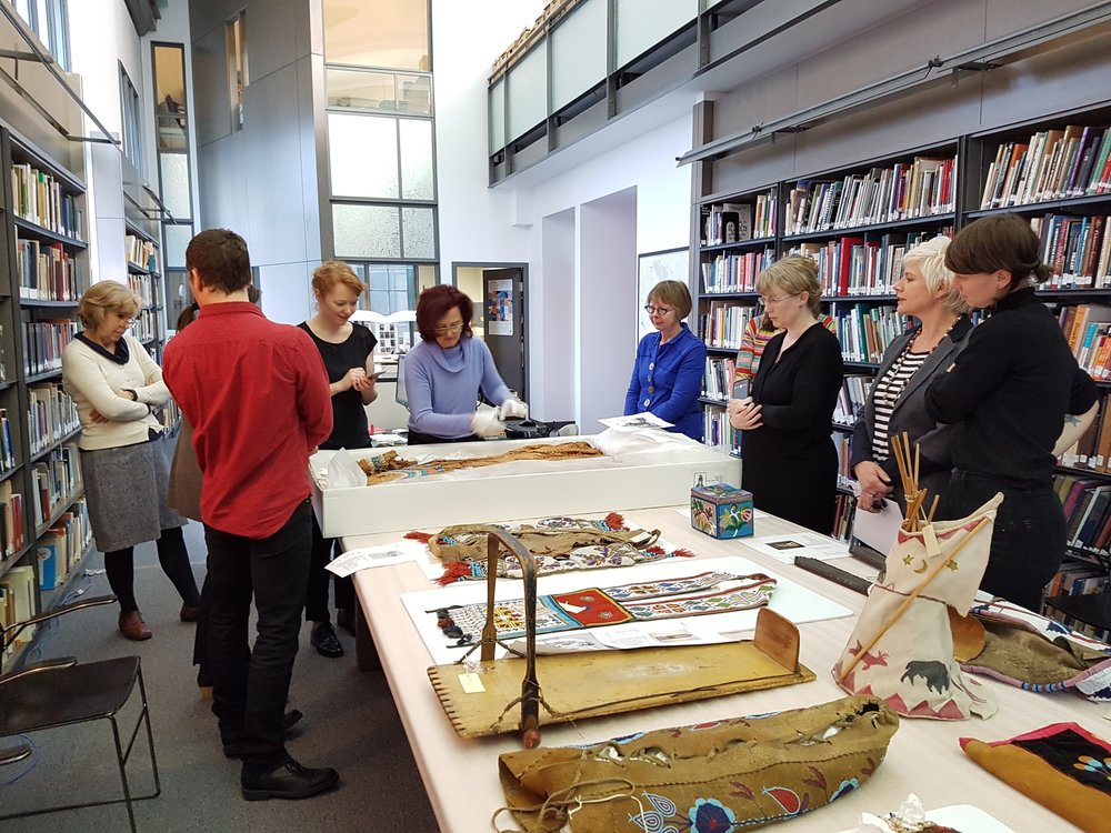 The Object Lives group examining a Nitsitapi embroidered hide dress, from the Hayter Reed collection, with the assistance of Guislaine Lemay.