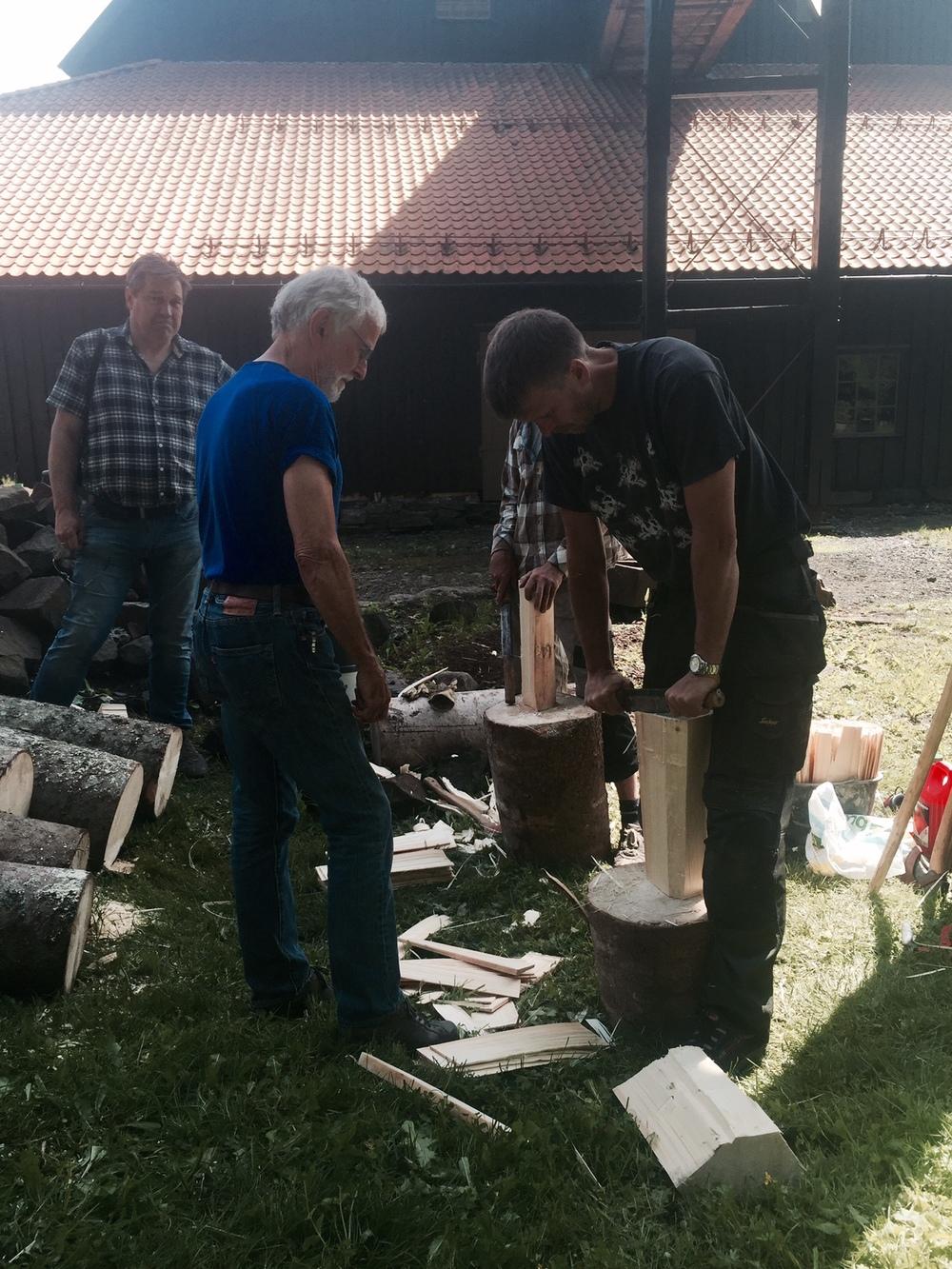 Lars N. Løvdal fra Sollie Bygg viser besøkende under Smed- og Håndverksmessen på Næs Jernverk hvordan en håndkløyver takspon.