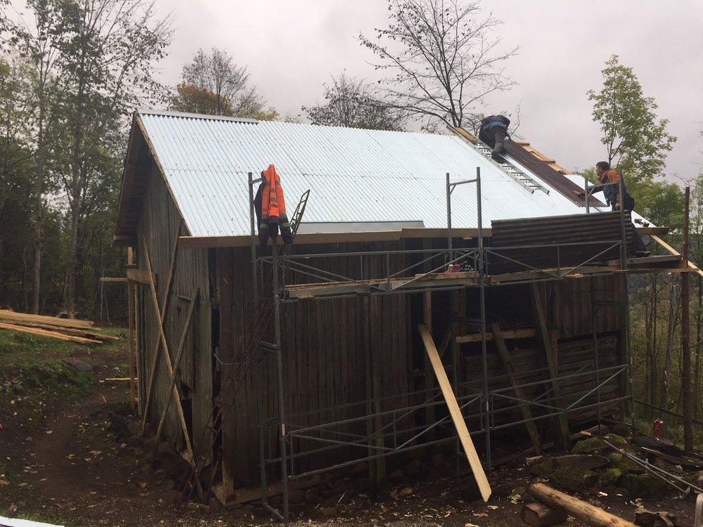 Lars N. Løvdal og Lars I. Abrahamsen fra Sollie Bygg AS i gang med å legge nye bølgeblikksplater på uthusets vest side.