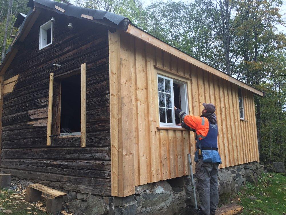 Lars I. Abrahamsen fra Sollie Bygg AS i gang med å sette inn de nye vinduene i innhuset.