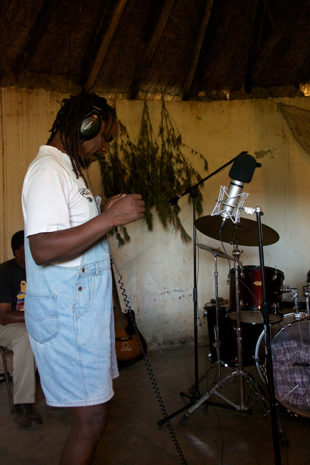 Ambrose doing dub reggae at the Siteki hut recordings.  Yes that is Ganja drying on the walls..jpg