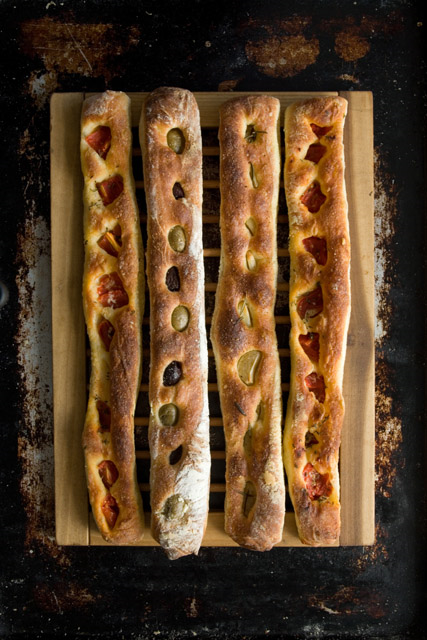 STRECCI WITH TOPPINGS   Strecci is made from our pizza bianca dough. The foot long flat bread is soft and chewy with a thin crust coated with olive oil and lightly salted. We top our strecci with a variety of seasonal toppings such as tomatoes, artichokes, olives and garlic.