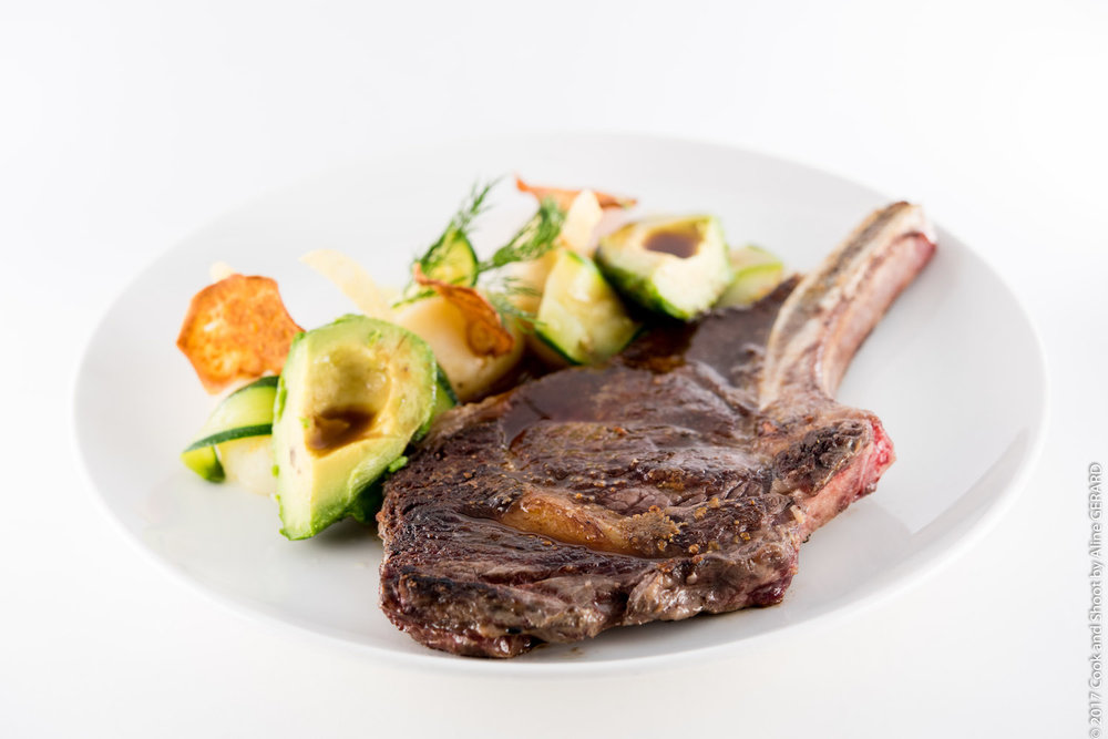 La Côte de Boeuf bio (viande française) à la plancha, (+ 450g) tubes de pommes de terre et chlorophylle comme un os à moelle, salade croquante, vinaigrette au jus de viande et perles de roquette