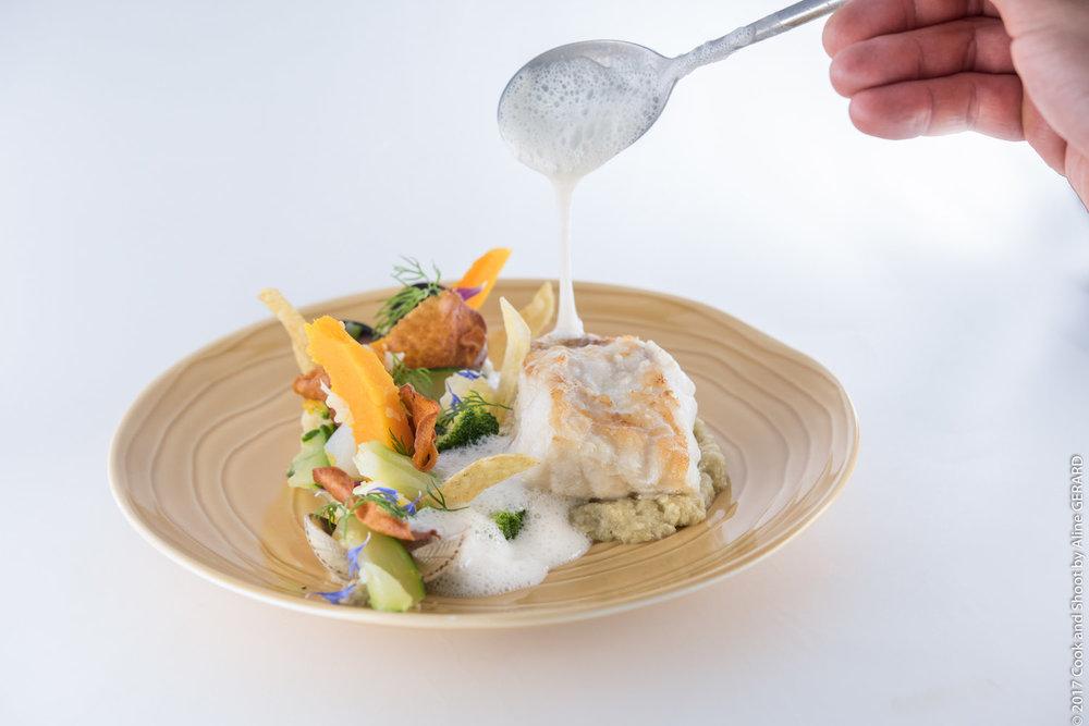 Le Médaillon de Lotte rôtie aux palourdes, légumes glacés —crémeux de fenouil, émulsion de jus marin