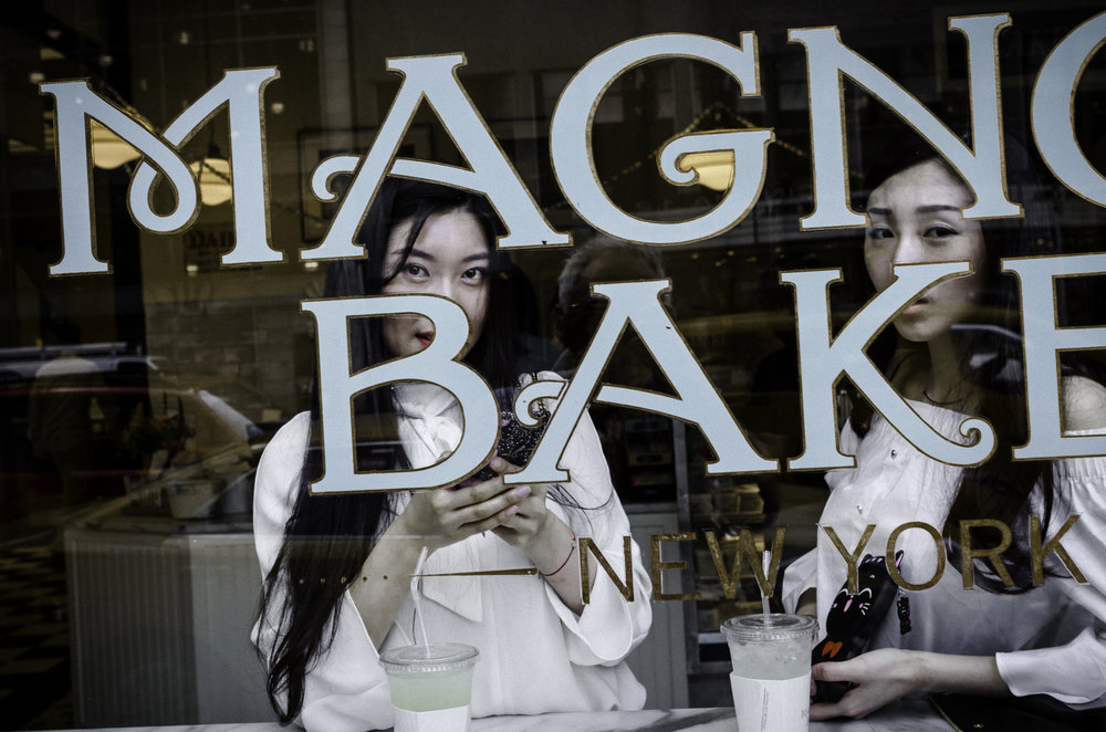 Asian_Women_in_Magnolia_Bakery_Window_57th_St_NYC_2017.jpg
