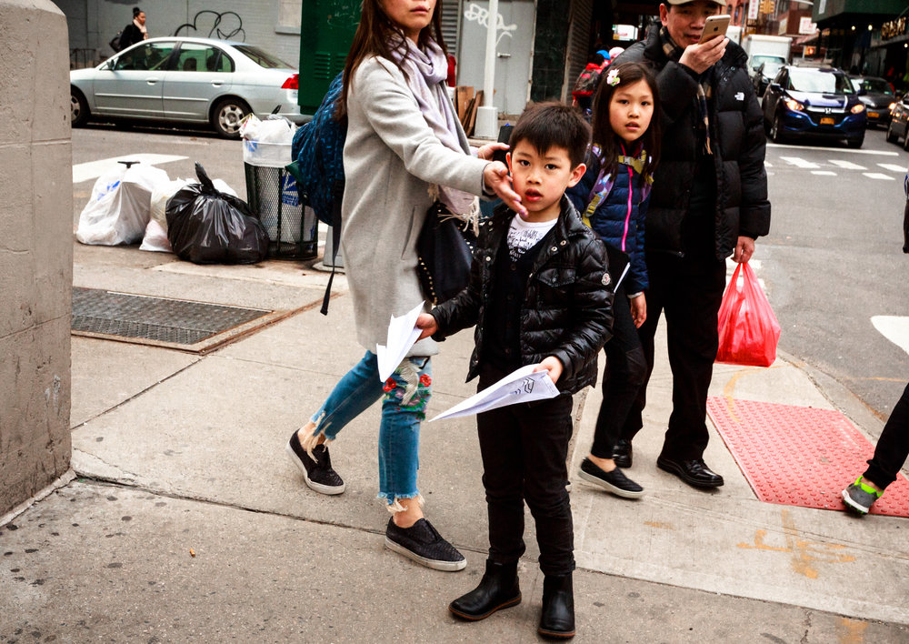 Chinese_Boy_With_Paper_Airplanes_Proteected_by_Mother_Chinatown_NYC_2017.jpg