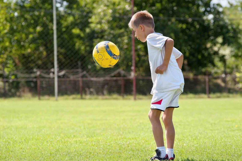 child-playing-soccer-on-a-soccer-field-controling-a-ball.jpg