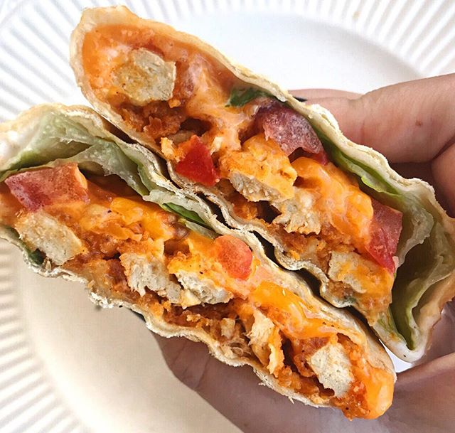 "Spice up your life!!!! 🔥 I made these buffalo ""chicken"" wraps for lunch AND dinner yesterday and I'm pretty sure I'll be doing that same thing today!  Vegetarian Buffalo ""Chicken"" Wraps with Gardein Crispy Tenders  Makes 1 serving  1 9-inch tortilla 2 Gardein Crispy Tenders 1 tbsp.+ Buffalo sauce  2 tbsp. Ranch 1/3 cup shredded cheddar Lettuce Tomato  Directions: Cook Gardein Crispy Tenders to package directions. Cut tenders in half lengthwise, then toss in a bowl with at least 1 tbsp. Buffalo hot sauce until coated Spread 2 tbsp. ranch dressing on a 9 in. tortilla  In the centre of the tortilla, add lettuce, tomato, 1/3 cup of cheese, and tenders.  Roll tortilla and eat as is, or pop it into a panini press to heat throughout."