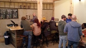 The tasting room is like being in a Maine camp with rugged timbers, tasteful decorative items, and a brick hearth with roaring stove.