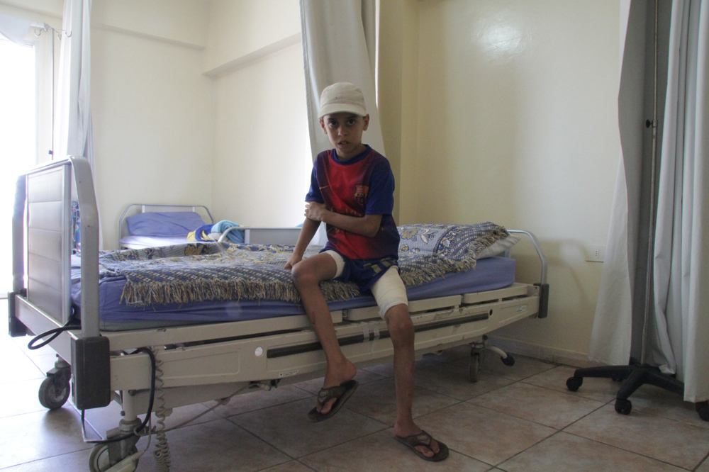 A Syrian boy, wounded by government airstrikes, seeks medical attention in Tripoli, Lebanon. Since fighting began in 2011, nearly four million Syrians have fled for places like Lebanon, Turkey, Jordan, and Iraq. (2013, Medium)