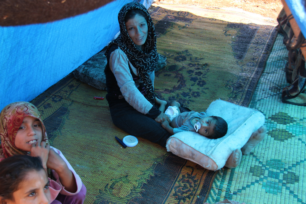 A mother, displaced by fighting in Aleppo, changes her son's diaper near the Bab Al Hawa Crossing in Syria. (2013, Medium)