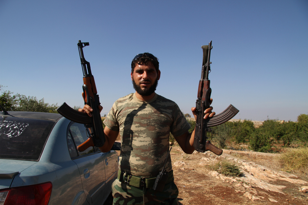 A rebel soldier displays his weapons in a field near Bab Al Hawa, Syria. (2013, Cool Hunting)