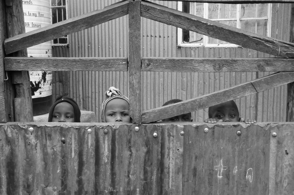 Four children peek over a corrugated fence  in the Kibera neighborhood of Nairobi, Kenya . (2012)
