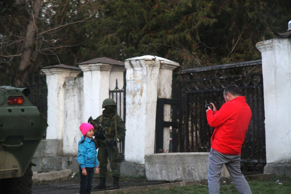 A father photographs his daughter in front of Russian troops stationed on the Crimean Peninsula; Simferopol, Ukraine. (2014,  Guernica Magazine )