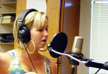 A pop filter (the large, black disc) is used during a recording session.
