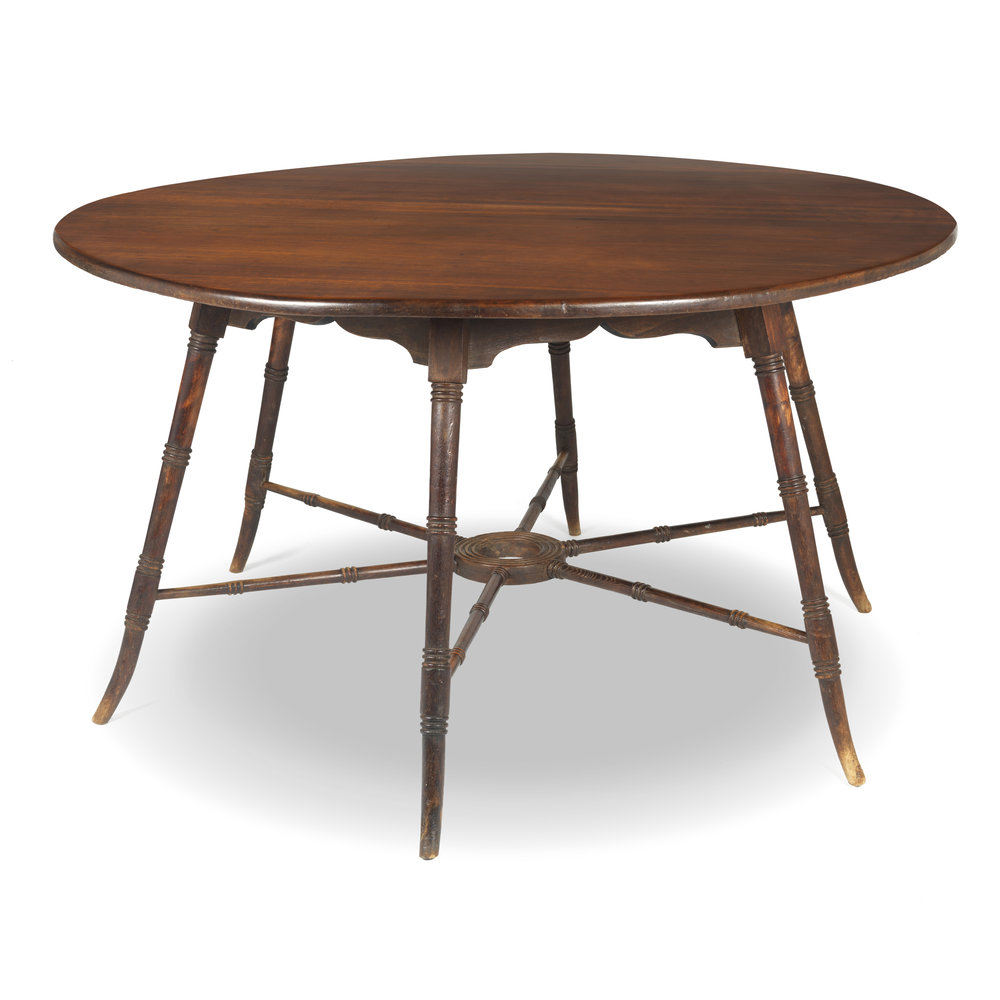 English circular table, in the manner of E.W. Godwin, with six splayed legs. The stretchers are joined by a central, turned ring.  Exotic pine, around 1870.  130cm diameter.  Available.