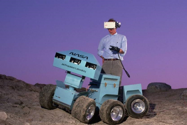 1988Andrew Mishkin wearing a 3-D virtual display helmet that is connected to a six-wheeled roving vehicle.