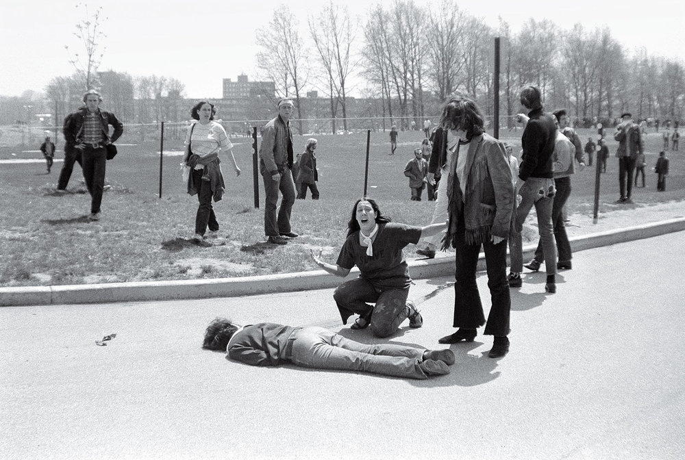 """Kent State Shooting"" 1970 John Paul Filo  ""The shooting at Kent State University in Ohio lasted 13 seconds. When it was over, four students were dead, nine were wounded, and the innocence of a generation was shattered. The demonstrators were part of a national wave of student discontent spurred by the new presence of U.S. troops in Cambodia. At the Kent State Commons, protesters assumed that the National Guard troops that had been called to contain the crowds were firing blanks. But when the shooting stopped and students lay dead, it seemed that the war in Southeast Asia had come home. John Filo, a student and part-time news photographer, distilled that feeling into a single image when he captured Mary Ann Vecchio crying out and kneeling over a fatally wounded Jeffrey Miller. Filo's photograph was put out on the AP wire and printed on the front page of the New York Times. It went on to win the Pulitzer Prize and has since become the visual symbol of a hopeful nation's lost youth. As Neil Young wrote in the song ""Ohio,"" inspired by a LIFE story featuring Filo's ­images, ""Tin soldiers and Nixon coming/ We're finally on our own/ This summer I hear the drumming/ Four dead in Ohio."" -- TIME MAGAZINE"