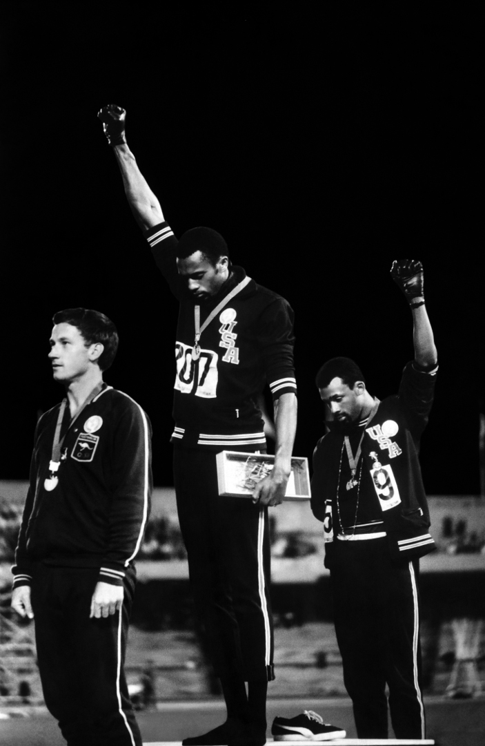 """Black Power Salute"" 1968 John Dominus  ""The Olympics are intended to be a celebration of global unity. But when the American sprinters Tommie Smith and John Carlos ascended the medal stand at the 1968 Games in Mexico City, they were determined to shatter the illusion that all was right in the world. Just before ""The Star-Spangled Banner"" began to play, Smith, the gold medalist, and Carlos, the bronze winner, bowed their heads and raised black-gloved fists in the air. Their message could not have been clearer: Before we salute America, America must treat blacks as equal. ""We knew that what we were going to do was far greater than any athletic feat,"" Carlos later said. John Dominis, a quick-fingered life photographer known for capturing unexpected moments, shot a close-up that revealed another layer: Smith in black socks, his running shoes off, in a gesture meant to symbolize black poverty. Published in life, Dominis' image turned the somber protest into an iconic emblem of the turbulent 1960s."" --- TIME MAGAZINE"