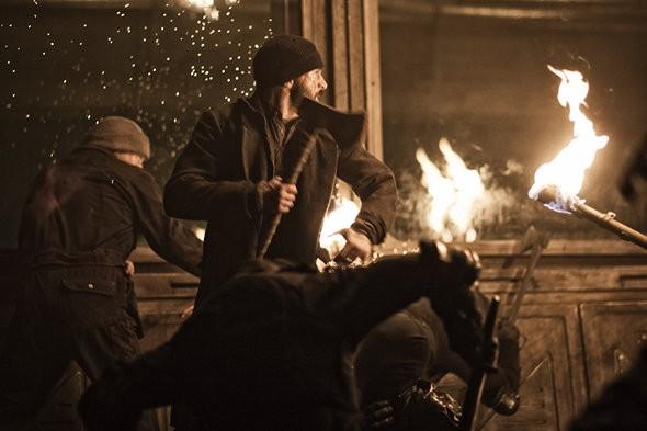 Torches illuminate the fight scene through a train car.