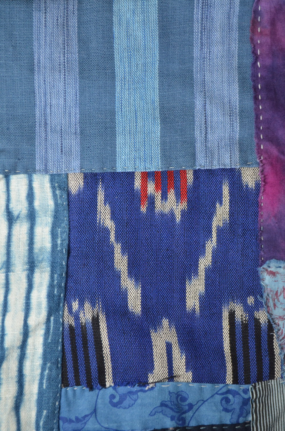 scraps of ikat, indigo shibori and stitched in the boro manner