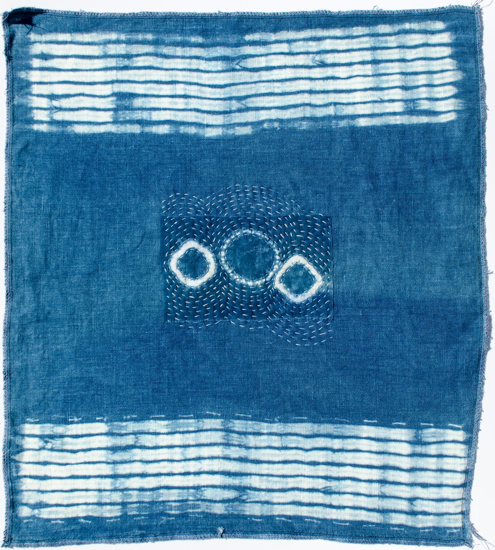 Visible mending on a linen using a scrap of shibori dyed cotton