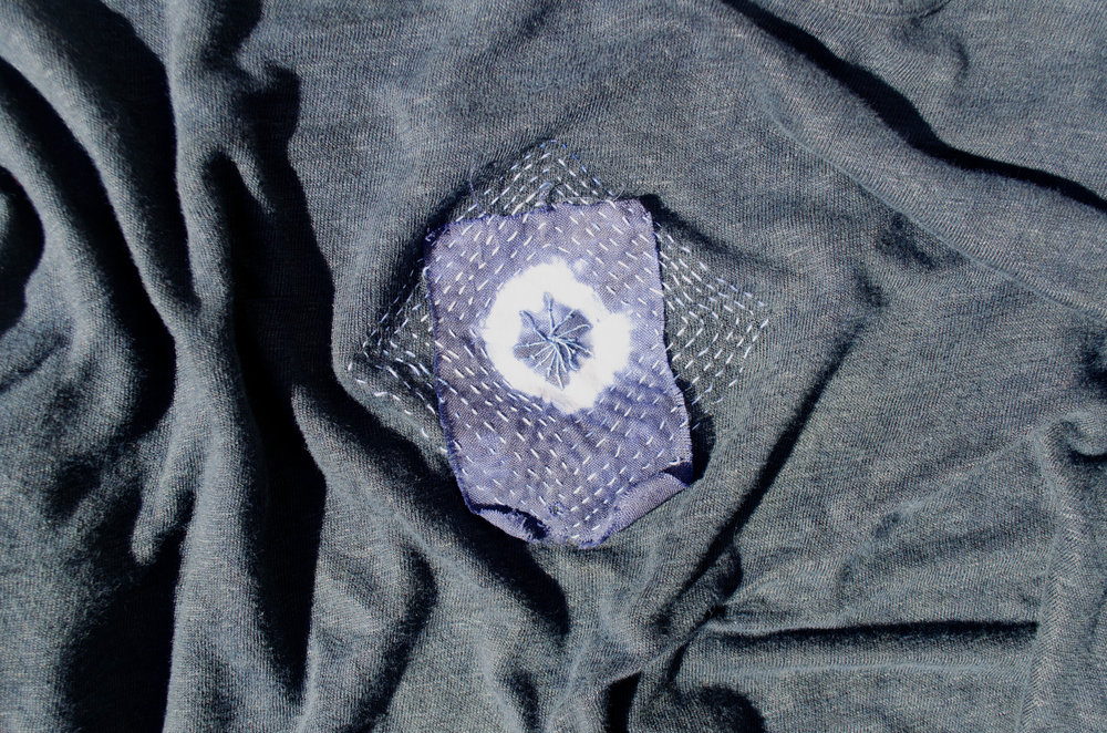 Sweater with a visible mend using a shibori dyed cotton patch