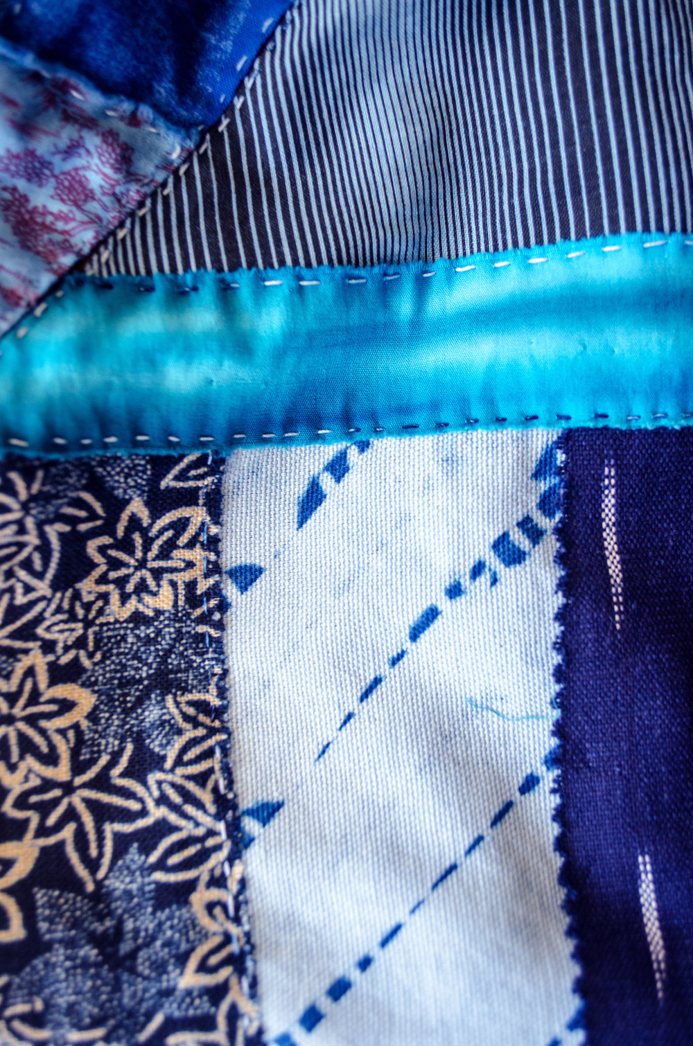 Cotton, folded, tied and dipped in the indigo vat before handstitching