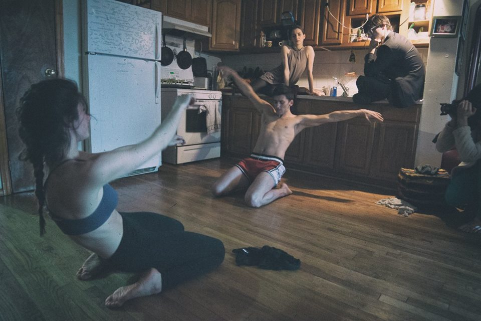 "Lia Bentley and Adam Robert Dickerson dance in a kitchen. Dancer Vera Paganin and composer Wes Braver watch from ""onstage;"" Keenan Parry films. Credit Joe Desimone."
