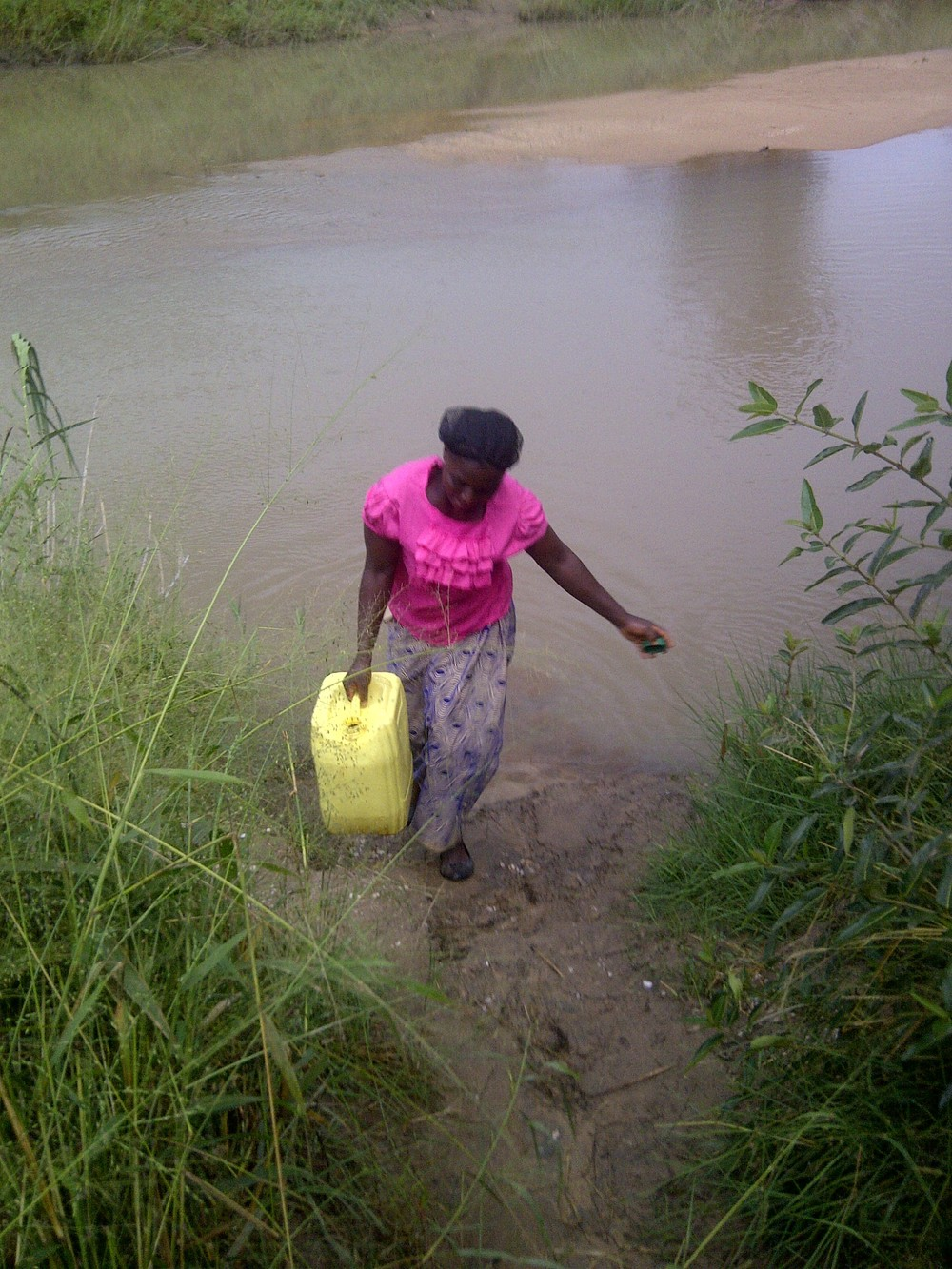 A lady gathers water for her family in Sichimwa, Zambia.