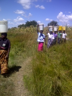 Women walking the distance to collect their daily water in the village of Mayoba.