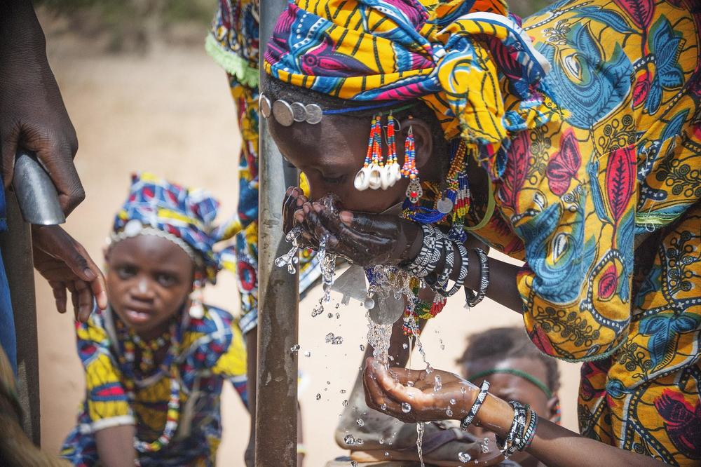 This beautiful image shows a woman in Niger enjoying fresh water from the local well. Photo by Jerry Atnip.