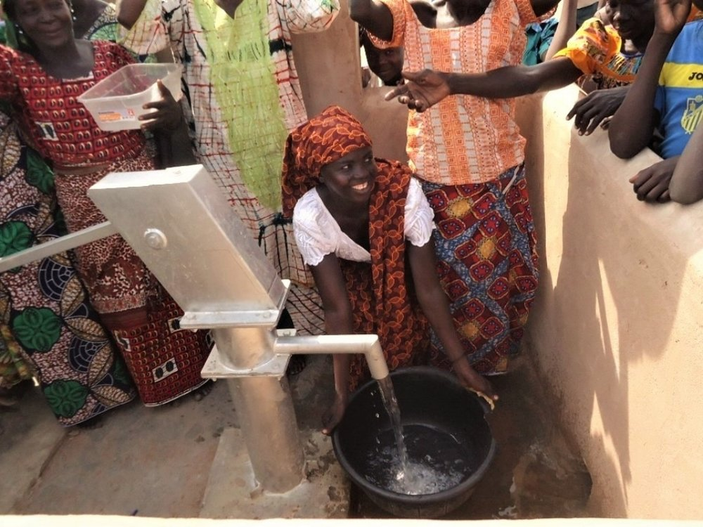 A woman near Kelo, Chad draws clean water from a Living Water Project well for the first time - January, 2017