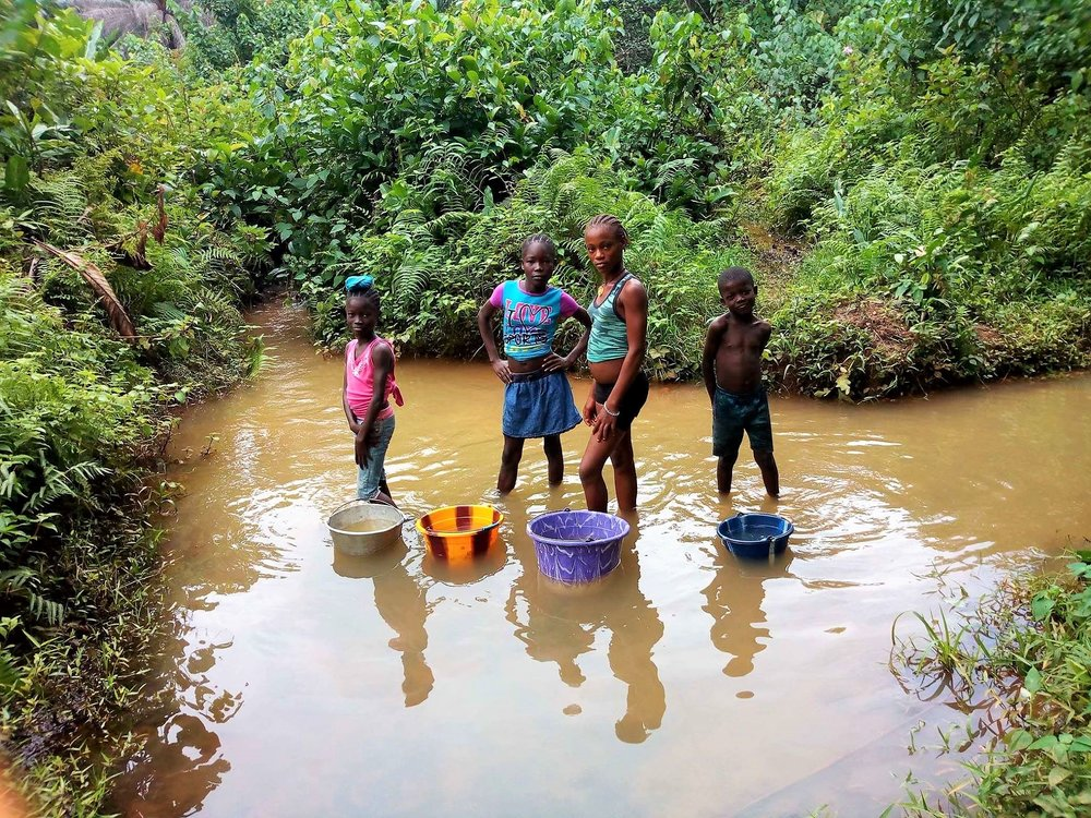 Local children gather water from the only water source they had prior to the well.