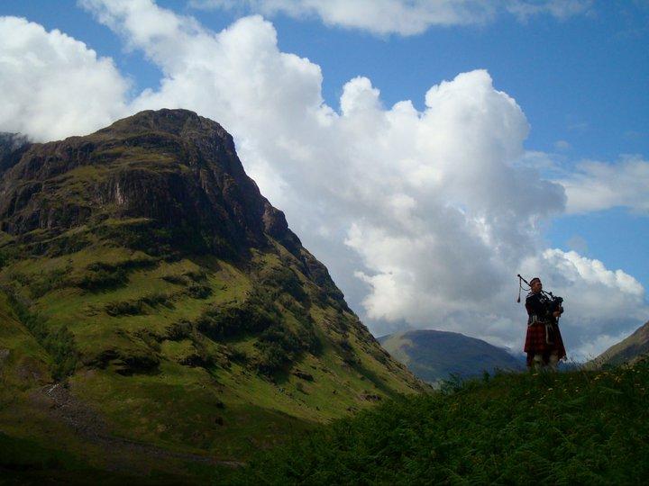 Un gaitero en medio de las montañas escocesas.