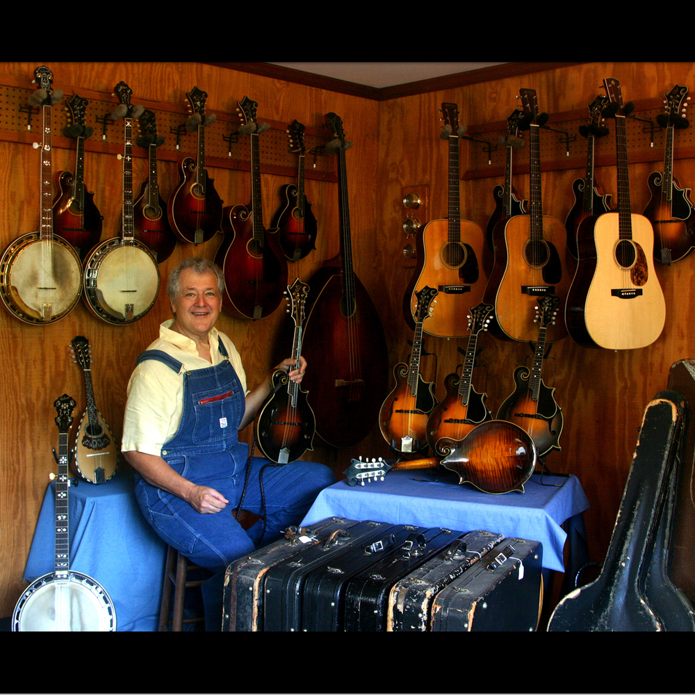 Tony Williamson surrounded by new and vintage instruments including  Lloyd Loar mandolins, Martin guitars and Gibson banjos. It's not just MANDOLIN Central!