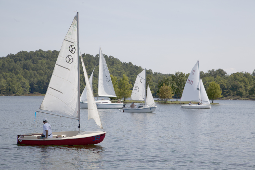 Sailors jockey for position in light winds before the start of a race in the 2013 Mountain Mama Hospice Regatta.