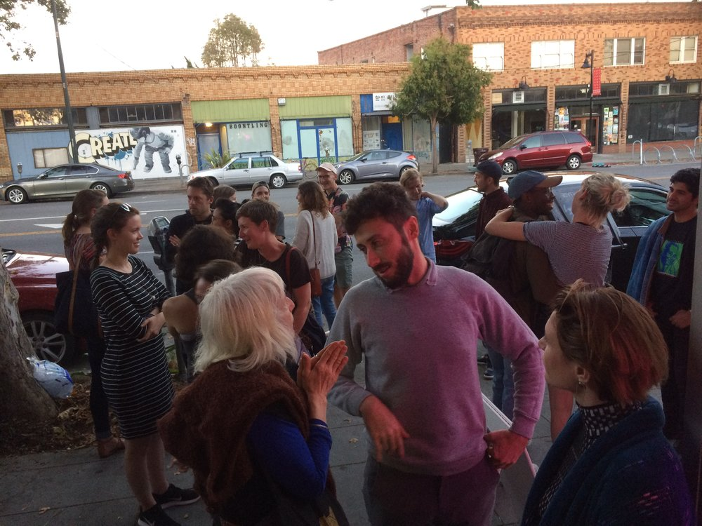 Guests mingle outside Royal Nonesuch Gallery while artists Woody Othello and Ivy Haldeman prepare their presentations. -July 2017