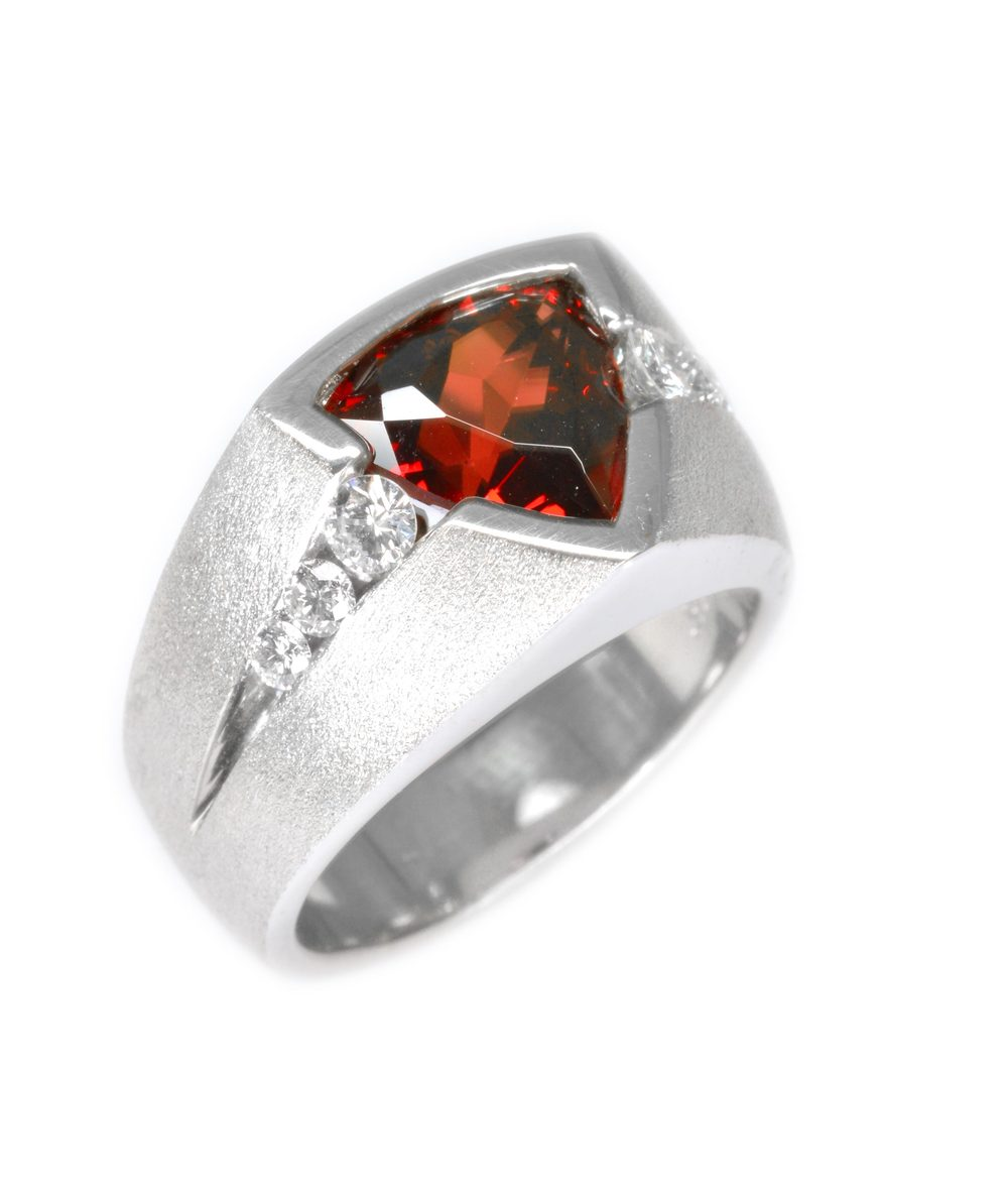 sterling silver ring set with a fiery-red Mozambique garnet and channel set diamonds with a textured finish, designed by Jason Baskin.