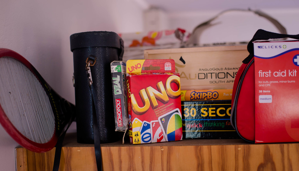 A selection of games, a first aid kit, flyswatter and pair of binoculars